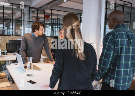 Team of young designers working together in office. Diverse business executive standing at a table working on new - Stock Photo