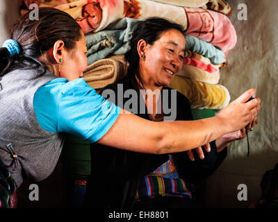 Mother and daughter looking at photos on a digital camera in Lo Manthang, Mustang, Nepal. - Stock Photo