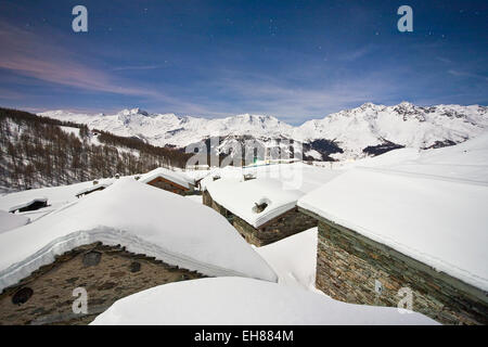 Group of mountain huts covered in snow under a starry night in Valle Spluga, Vachiavenna, Lombardy, Italy, Europe - Stock Photo
