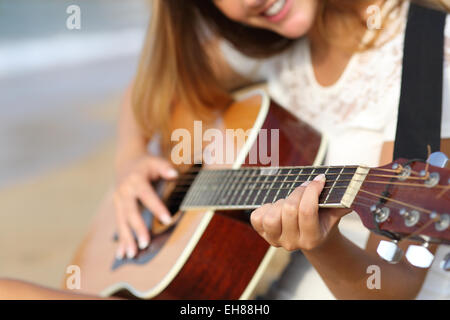 Close up of a woman playing guitar on the beach in a summer sunny day - Stock Photo