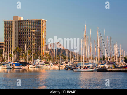 Waikiki, Hawaii, with sailboats in Ala Moana harbour and Hilton Hawaiian Village resort behind - Stock Photo