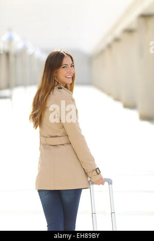 Traveler tourist woman walking and looking at camera through a corridor of an airport - Stock Photo
