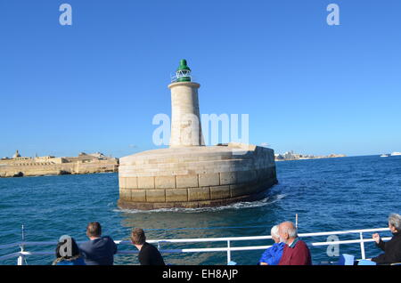 Malta, Valletta. From the sea into the Grand Harbour past the harbour walls and a lighthouse go a boatful of tourists. - Stock Photo
