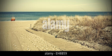 Retro toned panoramic photo of a beach, old film filter applied. - Stock Photo