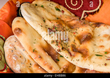 The traditional way to bake Naan, an Indian yeasted flat bread, is in a clay or earthen oven. - Stock Photo