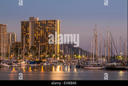 Skyline of Waikiki, Honolulu at night with Ala Moana harbor and Hilton Hawaiian Village resort hotels - Stock Photo