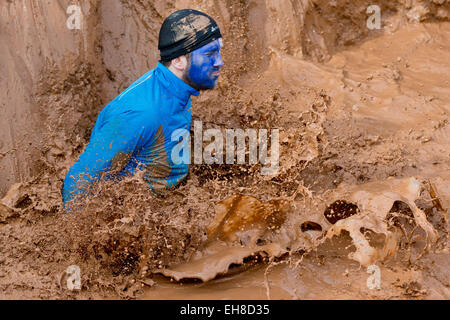 A participant tries to overcome a mud pit   during the extreme course event 'Braveheart-Battle' in Muennerstadt,Germany, - Stock Photo
