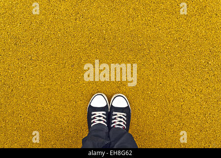 Sneakers from above. Man standing at yellow asphalt pavement as copy space - Stock Photo