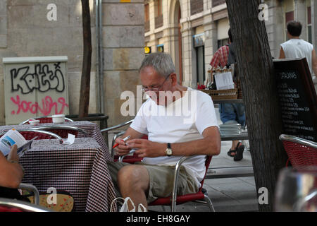 Man checking the bill, sitting at table of outdoor café in El Raval in the centre of Barcelona - Stock Photo