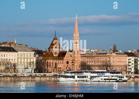 Calvinist church with a Danube river cruise boat in the foreground, Budapest, Hungary - Stock Photo