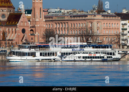 Danube river cruise boat, Budapest, Hungary with Calvinist church in the background - Stock Photo
