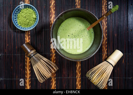 Bowl of Matcha with a Chasen a Chashaku and a bowl of Matcha powder on a place mat - Stock Photo