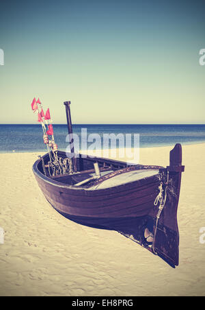 Retro filtered picture of fishing boat on the beach. - Stock Photo