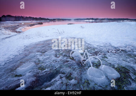 Colorful winter evening skies and moonrise by the Oslofjord,  at Oven in Råde kommune, Østfold fylke, Norway. - Stock Photo