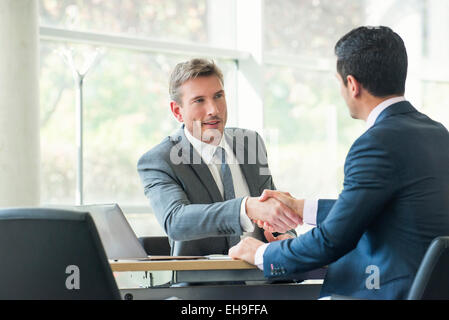 Businessmen shaking hands in meeting - Stock Photo