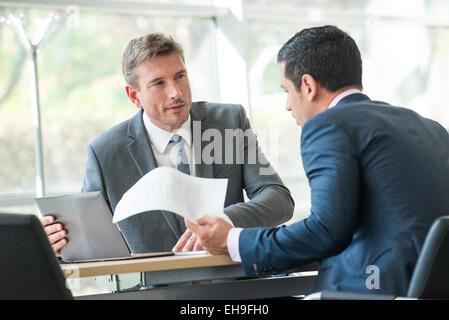 Businessmen negotiating in meeting - Stock Photo