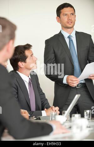 Businessman giving presentation at meeting - Stock Photo