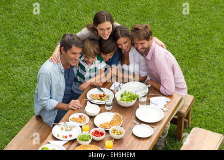 Family and friends huddle for group picnic photo - Stock Photo