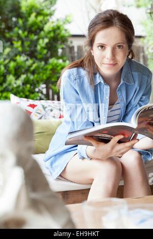 Young woman reading magazine - Stock Photo