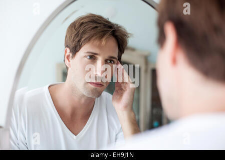 Man looking at self in mirror with concerned look - Stock Photo