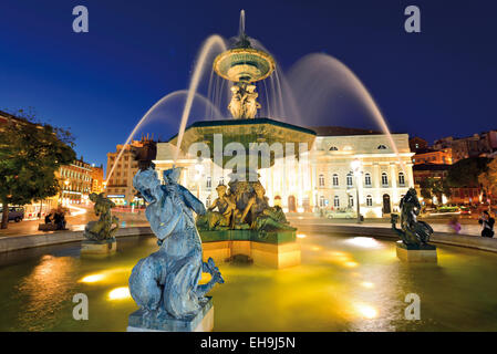 Portugal, Lisbon: Nocturnal illuminated water fountain at Rossio ou Pedro IV Square in downtown - Stock Photo