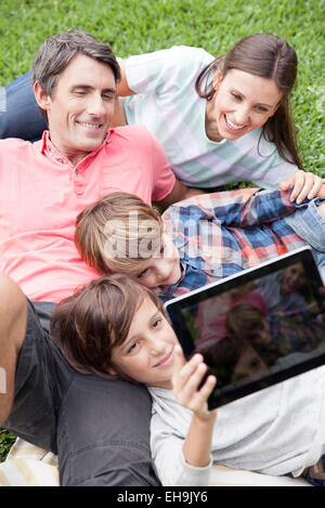 Boy photographing family with digital tablet camera - Stock Photo