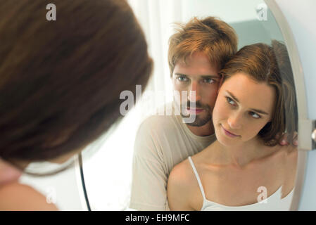 Couple cheek to cheek, looking at each other in mirror - Stock Photo