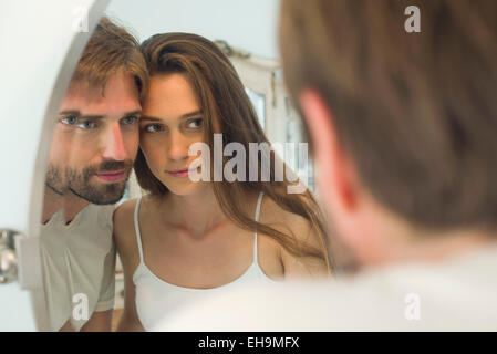 Couple cheek to cheek looking into mirror together - Stock Photo