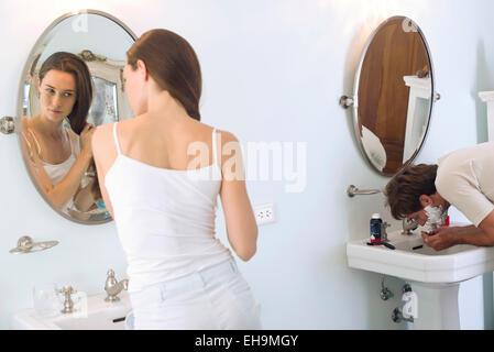 Woman brushing hair, husband shaving - Stock Photo