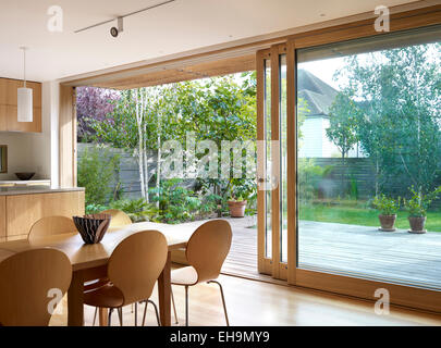 Wooden dining table and chairs in front of large sliding glass doors, residential house, Lloyd Close, UK - Stock Photo