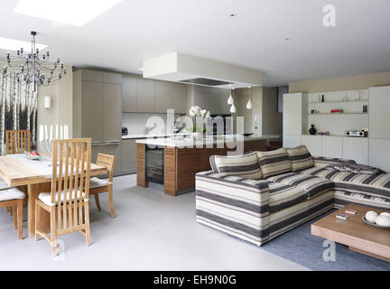 Modern open plan kitchen, dining area and living area with striped corner sofa in Stevenage Road home, UK - Stock Photo