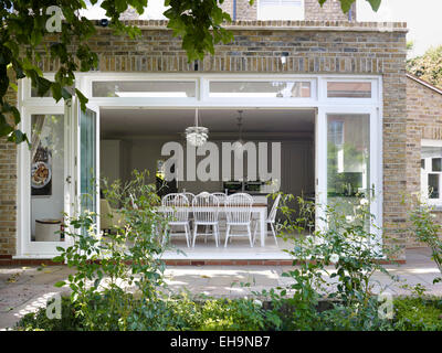 Garden with view through double doors to kitchen and dining area of Edenhurst Road home, UK - Stock Photo
