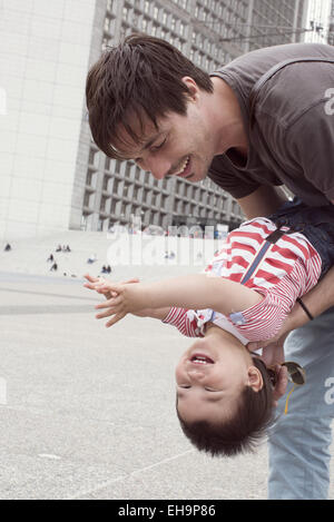 Father holding young son upside down, both laughing - Stock Photo