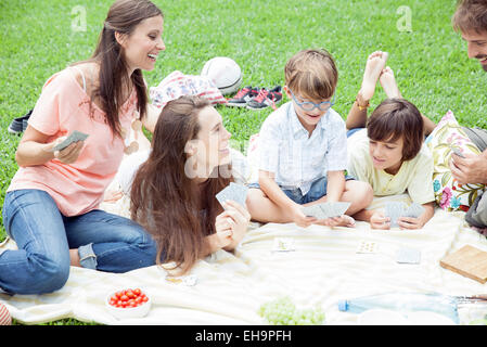 Family having picnic and playing card game - Stock Photo