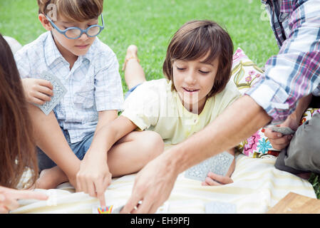 Boys playing cards at family picnic - Stock Photo