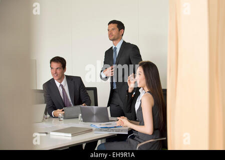 Executives meeting in conference room, viewed through doorway - Stock Photo