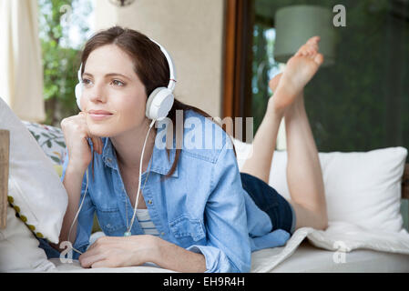 Young woma lying on stomach, listening to headphones - Stock Photo