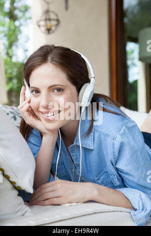 Young woman listening to headphones, portrait - Stock Photo