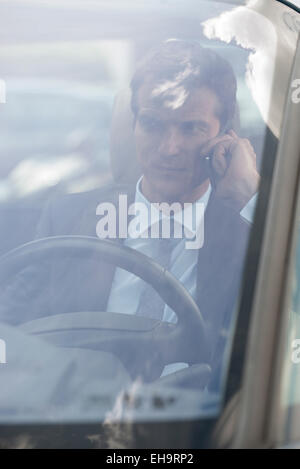 Businessman talking on cell phone while driving - Stock Photo