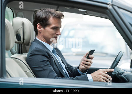Man looking at cell phone while driving - Stock Photo