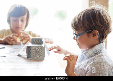 Boys building house of cards together - Stock Photo