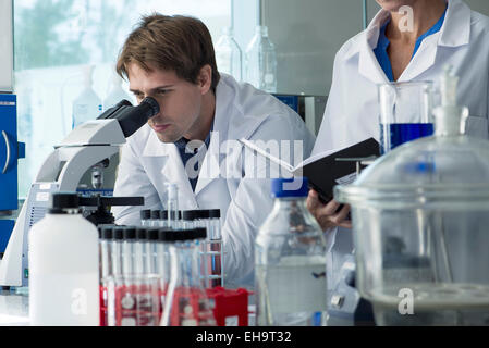 Scientist looking through microscope in laboratory - Stock Photo