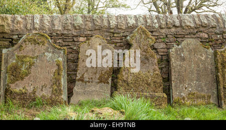 Ancient and weathered headstones in the churchyard of Hardraw Church, near Hawes, North Yorkshire, England, Great - Stock Photo