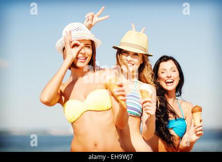 girls in bikini with ice cream on the beach - Stock Photo