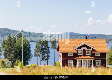 Traditional Swedish country house painted in falu red on shores of Lake Siljan in Tallberg, Sweden - Stock Photo