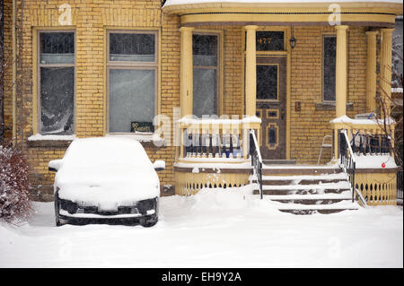 A snow covered car parked in a home driveway in Canada. - Stock Photo