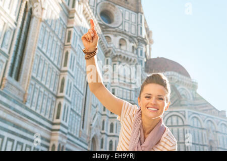Happy young woman pointing in front of cattedrale di santa maria del fiore in florence, italy - Stock Photo