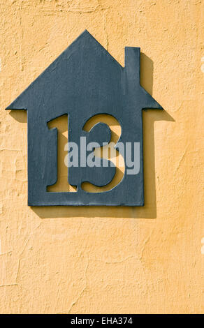 House number 13 on a yellow wall - Stock Photo