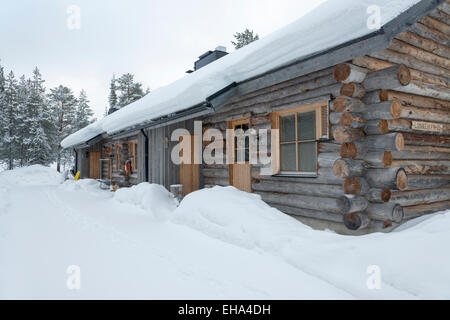 A log cabin in the snow in winter. Holiday rental accommodation in the ski resort of Levi, Lapland, Finand - Stock Photo