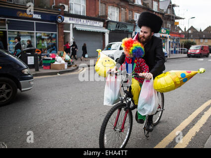 Thursday, March 5, 2015  An Ultra-Orthodox Jewish man walks cycles along with his child dressed in fancy dress to - Stock Photo